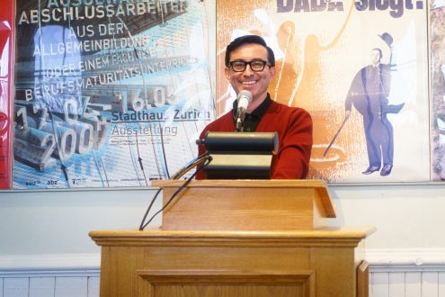 Ruben Quesada smiles at podium in front of abstract posters at Cafe Anna